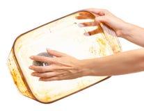 妇女洗着与金属厨房海绵的油腻肮脏的玻璃盘子 图库摄影
