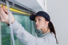 妇女测量的窗架 库存照片