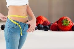 妇女测量的腰部的中央部位由代表减重的果子的 库存图片