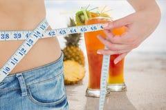 妇女测量的腰部的中央部位部分用汁液在背景中 免版税库存图片