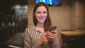 妇女浏览她的手机的互联网并且看照相机和微笑 影视素材