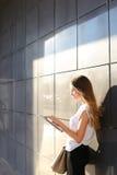 妇女浏览片剂在商业中心 免版税图库摄影