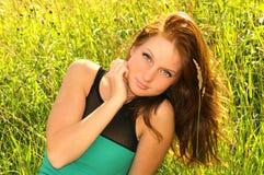 妇女浪漫与在绿色领域草的长的棕色头发 库存照片