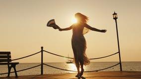 妇女海上遇见黎明 情感地转动与一个帽子在他的手上在码头 旅行概念梦想  免版税库存照片