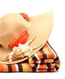 妇女海滩帽子、明亮的毛巾和seashel 图库摄影