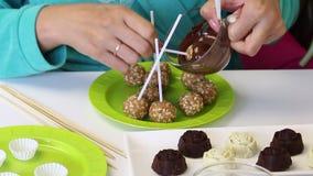 妇女浸洗popcake宿营入熔化巧克力 其次在板材现成的空白 股票视频