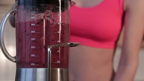 妇女混和的莓果、香蕉和杏仁挤奶做一名健康绿色圆滑的人 影视素材