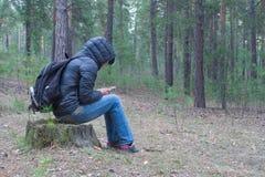 妇女清早坐在森林和ch的一个树桩 库存照片