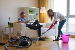 妇女清洁在家难倒,当她的坐在长沙发时的懒惰人 免版税库存图片