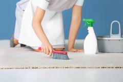 妇女清洁地毯 免版税库存图片