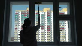 妇女清洁窗口的剪影 股票录像