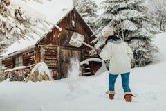 妇女清洁雪的背面图从她的围场的 库存照片