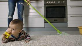 妇女清洗地板的` s腿特写镜头在婴孩附近
