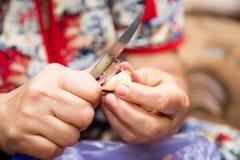 妇女清洗大蒜与刀子 库存照片
