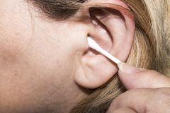 妇女清洗她的耳朵与棉花棒 免版税库存照片