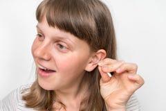 妇女清洗她肮脏的耳朵与棉花棒 库存图片