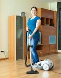 妇女清洗与吸尘器 免版税库存照片