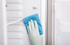 妇女清洁冰箱 免版税库存照片