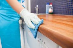 妇女清洁厨房工作台面 图库摄影