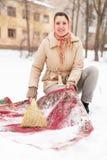 妇女清洗地毯与雪 免版税库存图片