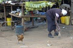妇女清洗她的在她小的商店前面的街道 免版税图库摄影