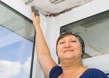 妇女清洗油灰与沙纸 免版税库存照片
