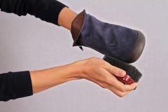 妇女清洁油鞣革鞋子 绒面革穿上鞋子冬天关心 免版税库存照片