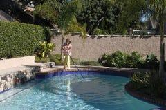 妇女清洁游泳池 免版税库存照片