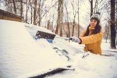 妇女清洁雪汽车挡风玻璃  免版税库存图片