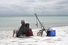 妇女渔在海滩的阴暗天 免版税库存照片