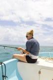 妇女渔在从小船的海洋 免版税库存图片