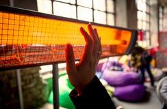妇女温暖的手特写镜头在红外加热器的 免版税库存照片
