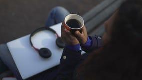 妇女温暖的手,拿着有芬芳热的饮料的杯子,当坐户外时 股票录像