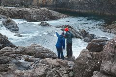 妇女游人在山河的河岸站立有小瀑布的 库存照片