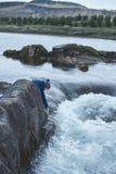妇女游人坐山河的河岸有小瀑布的 库存照片