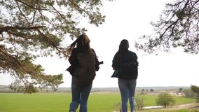 妇女游人审阅有背包的性感的女性旅客调直他们的胳膊支持的森林,享受自由 影视素材