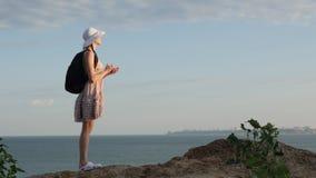 妇女游人寻找与一个GPS导航员的根在智能手机,发现方式 海洋在日落的海海滩 股票视频
