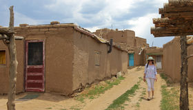 妇女游人步行一条街道在Taos镇 免版税库存图片