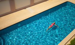 妇女游泳和放松在水池 免版税库存图片
