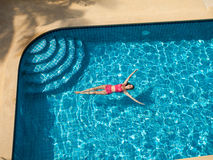 妇女游泳和放松在水池 免版税库存照片