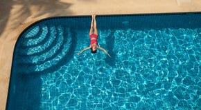 妇女游泳和放松在水池 免版税图库摄影