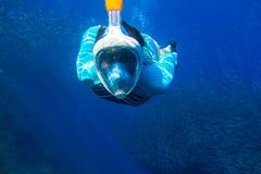 妇女游泳在蓝色海 潜航在正面面具的女孩 与鱼学校水下的照片的废气管 免版税图库摄影