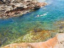 妇女游泳在透明的水中 免版税库存照片