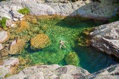 妇女游泳在水自然池塘 图库摄影