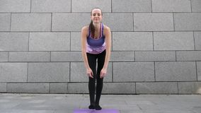 妇女滚动单独的瑜伽席子入照相机在灰色都市城市背景 自由、健康和瑜伽概念 关闭射击 股票录像