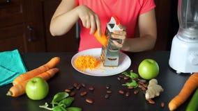 妇女滤栅新鲜的红萝卜在厨房里 股票录像