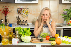妇女激动哀伤的在厨房用桌上 免版税库存图片