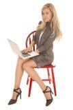 妇女灰色企业礼服坐膝上型计算机微笑 免版税库存图片