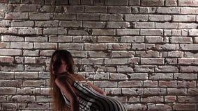 妇女灵活在高跟鞋跳舞twerk对砖墙 慢的行动 股票录像