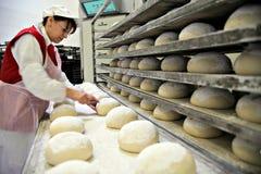 妇女烘烤面包 图库摄影